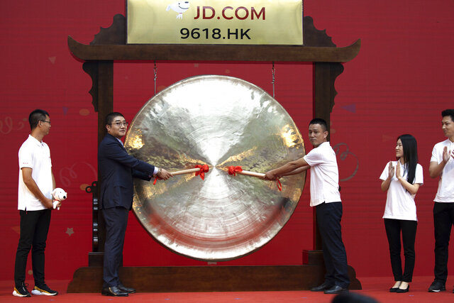 Xu Lei, head of JD Retail, second from left, sounds the gong to mark the listing of JD.com on the Hong Kong Stock Exchange at the JD.com headquarters in Beijing on Thursday, June 18, 2020. Chinese e-commerce firm JD.com's stock jumped nearly 6% on its debut in Hong Kong on Thursday after the firm raised $3.9 billion in a share sale. (AP Photo/Ng Han Guan)