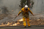 A firefighter battles a fire near Burrill Lake, Sunday, Jan. 5, 2020. Milder temperatures Sunday brought hope of a respite from wildfires that have ravaged three Australian states, destroying almost 2,000 homes. (AP Photo/Rick Rycroft)