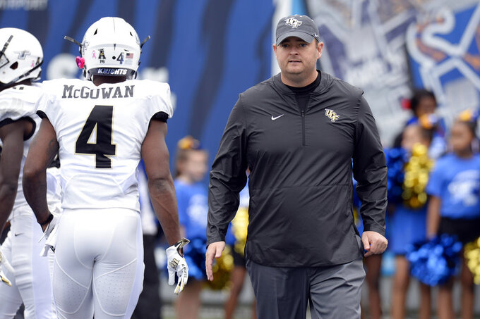 FILE - In this Oct. 13, 2018, file photo, Central Florida head coach Josh Heupel watches players warm up before an NCAA college football game against Memphis, in Memphis, Tenn. The seventh-ranked Knights (11-0, 8-0, No. 8 CFP) are one victory away from their second straight American Athletic Conference championship, a likely New Year's Six bowl bid and bolstering their argument that they are deserving of consideration for a berth in the College Football Playoff. None of that is possible, though, without beating Memphis (8-4, 5-3) in Saturday's AAC title game.(AP Photo/Mark Zaleski, File)