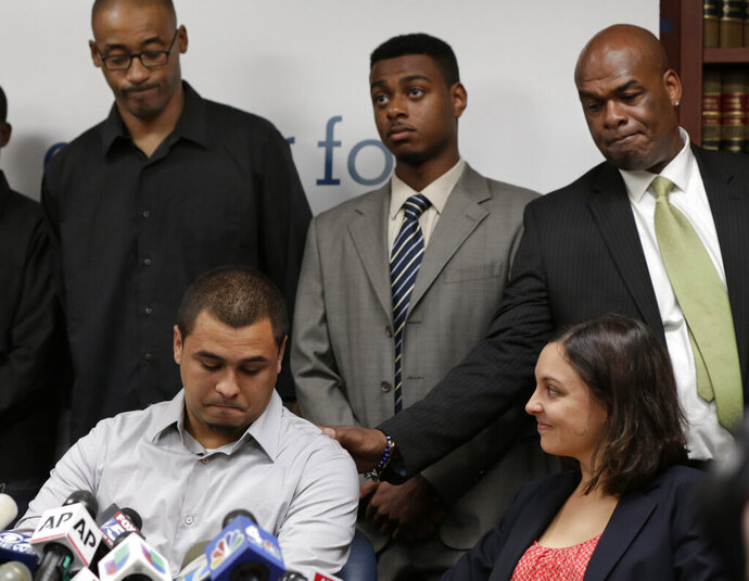 FILE - In this Aug. 12, 2013 file photo, plaintiff in the stop and frisk case David Ourlicht, seated left, is comforted by Merault Almonar, standing at right, father of plaintiff Devin Almonar, standing center, during a news conference at the Center for Constitutional Rights, in New York, after . U.S. District Judge Shira Scheindlin ruled that the New York Police Department deliberately violated the civil rights of tens of thousands of New Yorkers with its contentious stop-and-frisk policy. Standing at left is plaintiff Leroy Downes while attorney Jenn Borchetta listens, seated right. (AP Photo/Richard Drew, File)