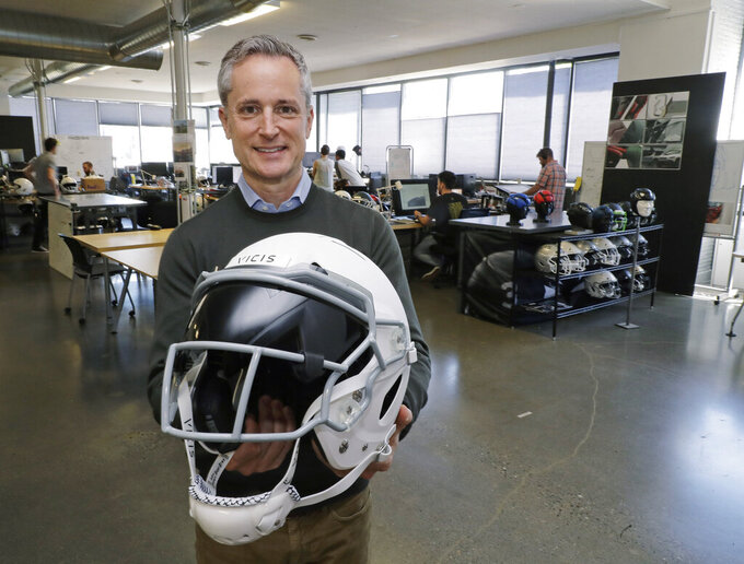 In this photo taken May 23, 2019, Dave Marver, CEO of VICIS, a Seattle-based company that makes football helmets, poses for a photo in Seattle as he holds one of the company's football helmets. VICIS announced on Monday, July 1, the cap is intended for use with youth flag football and the quickly expanding competitive 7-on-7 football played during the offseason for youth and high school programs. (AP Photo/Ted S. Warren)