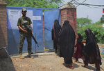 Pakistani paramilitary soldier stands guard while tribal women enter a polling station to vote during an election for provincial seats in Jamrud, a town of Khyber district, Pakistan, Saturday, July 20, 2019. Pakistan's northwestern tribal areas are holding their first-ever provincial elections. The seven tribal areas were merged last year as tribal districts into the northwestern Khyber Pakhtunkhwa province. Before that, the tribal areas were federally administered, and residents could only vote in the national assembly. (AP Photo/Muhammad Sajjad)