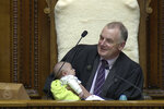 In this Wednesday, Aug. 21, 2019, image from video, New Zealand House Speaker Trevor Mallard cradles lawmaker Tamati Coffey's baby, Tutanekai Smith-Coffey, in his arms while presiding over a debate in parliament in Wellington, New Zealand. Mallard said Friday, Aug. 23, 2019, he's been trying to make parliament a more baby-friendly place since taking on the role nearly two years by adding baby chairs, family rooms and soon, a slide. He's also increased the flexibility around family leave for lawmakers. (Parliament TV via AP)