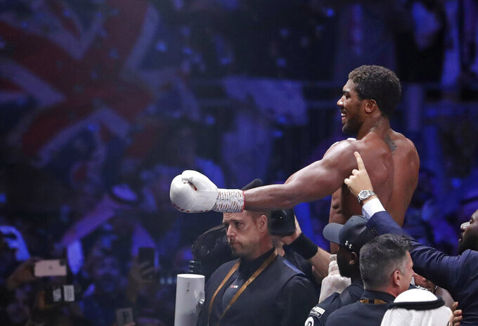 FILE - In this file photo dated Sunday Dec. 8, 2019, Britain's Anthony Joshua celebrates after beating Andy Ruiz Jr. to win their World Heavyweight Championship contest at the Diriyah Arena, Riyadh, Saudi Arabia.  Joshua was able to end his self-isolation on Wednesday Dec. 9, 2020, after his coronavirus test came back negative ahead of his world heavyweight clash with Kubrat Pulev at Wembley in London on upcoming Saturday Dec. 12, 2020. (AP Photo/Hassan Ammar, FILE)