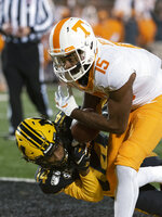 Tennessee wide receiver Jauan Jennings, top, scores a touchdown agaomst Missouri defensive back Adam Sparks during the second quarter of an NCAA college football game Saturday, Nov. 23, 2019, in Columbia, Mo. (AP Photo/L.G. Patterson)