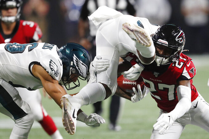 Atlanta Falcons strong safety Damontae Kazee (27) hits Philadelphia Eagles running back Corey Clement (30) during the first half of an NFL football game, Sunday, Sept. 15, 2019, in Atlanta. (AP Photo/John Bazemore)