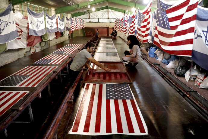 In this Saturday, Feb. 8, 2020 photo, workers print U.S. flags using a silkscreen, at the Diba Parcham Khomein factory in Heshmatieh village, a suburb of Khomein city, in central Iran. Workers at a small Iranian factory diligently add all 50 stars and 13 bars to American flags while carefully imprinting the Star of David on those of Israel. That's even as all their work is destined to go up in smoke. This factory serves as a major producer for the American and Israeli flags constantly burned at demonstrations in the Islamic Republic. (AP Photo/Ebrahim Noroozi)