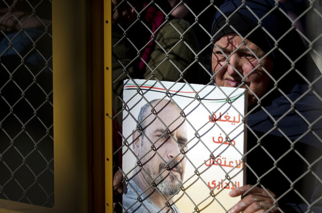 Rasila Zahran holds photograph of her son Ahmed Zahran , who has been on a partial hunger strike for nearly three months, outside Ofer military prison near the West Bank city of Ramallah, Thursday, Dec. 19, 2019. Zahran was arrested in February and is being held without charge in what is known as administrative detention. He is a member of the Popular Front for the Liberation of Palestine, a leftist group that Israel blames for a bombing in a settlement in August that killed a 17-year-old Israeli girl . The Arabic reads :