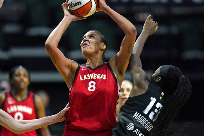 Las Vegas Aces' Liz Cambage (8) shoots over Seattle Storm's Ezi Magbegor in the first half of a WNBA basketball game Saturday, May 15, 2021, in Everett, Wash. (AP Photo/Elaine Thompson)