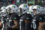 "Marshall players wear a ""75"" decal on their helmets as they take the field for an NCAA college football game against Middle Tennessee on Saturday, Nov. 14, 2020, in Huntington, W.Va. The game took place on the 50th anniversary of the 1970 Marshall plane crash that killed all 75 persons aboard. (Sholten Singer/The Herald-Dispatch via AP)"