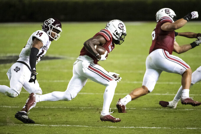 South Carolina wide receiver Shi Smith, center, carries the ball next to Texas A&M defensive back Keldrick Carper (14) during the second half of an NCAA college football game Saturday, Nov. 7, 2020, in Columbia, S.C. Texas A&M won 48-3. (AP Photo/Sean Rayford)