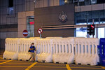 A journalist walks past the police headquarters in Hong Kong, Thursday, July 30, 2020. Hong Kong police have made their first major arrests under a new national security law, detaining four young people on suspicion of inciting secession. Police say they arrested three males and one female, aged 16 to 21, at three locations. All are believed to be students. (AP Photo/Kin Cheung)