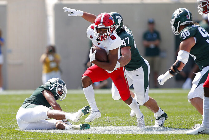 Youngstown State tailback Jaleel McLaughlin, center, rushes against Michigan State's Xavier Henderson, left, Jeff Pietrowski (47), and Jacub Panasiuk during an NCAA college football game, Saturday, Sept. 11, 2021, in East Lansing, Mich. Michigan State won 42-14. (AP Photo/Al Goldis)