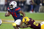 Arizona's Khalil Tate (14) slips the tackle of Arizona State's Jack Jones (21) during the first half of an NCAA college football game, Saturday, Nov. 30, 2019, in Tempe, Ariz. (AP Photo/Darryl Webb)