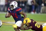 Arizona's Khalil Tate (14) slips the tackle of Arizona State's Jack Jones (21) during the first half of an NCAA college football game, Saturday, Nov. 30, 2019, in Tempe, Ariz. (AP Photo/Darryl Webb)