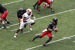 Cincinnati quarterback Desmond Ridder (9) is chased in the backfield by Miami (Ohio) defensive lineman Dominique Robinson (11) during the first half of an NCAA college football game Saturday, Sept. 4, 2021, in Cincinnati. (AP Photo/Jeff Dean)
