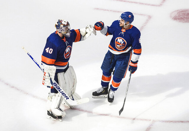 New York Islanders goalie Semyon Varlamov (40) and teammate Ryan Pulock (6) celebrate the team's win over the Tampa Bay Lightning in Game 3 of the NHL hockey Eastern Conference final, Friday, Sept. 11, 2020, in Edmonton, Alberta. (Jason Franson/The Canadian Press via AP)