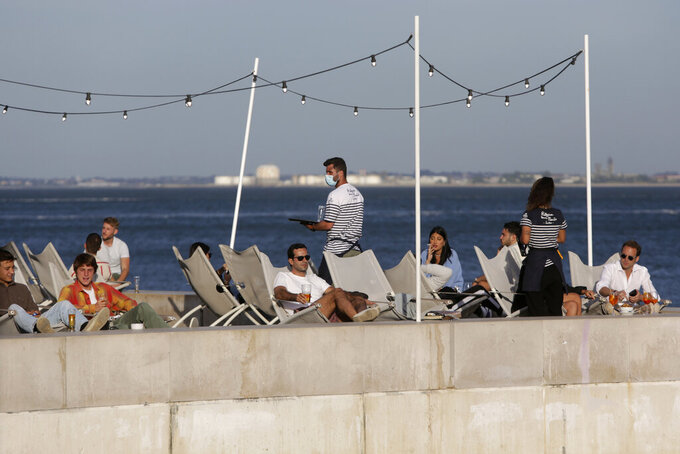"""FILE - In this Friday, June 4, 2021 file photo, people have drinks by the Tagus river in Lisbon as the sun sets. Two months after Portugal began to ease a prolonged lockdown, the Lisbon region is going into reverse due to a surge driven by the coronavirus' delta variant, which now accounts for more than 7 in 10 new infections in the capital. The country reported 1,556 new infections Thursday, June 24, 2021 — the highest number since Feb. 20. Just over 1,000 of them were in the Lisbon region. Officials say hospital admissions are increasing at a """"worrying"""" level. Portugal was the worst-hit country in the world, in terms of weekly infections, in January. But an extended lockdown contained the spread. (AP Photo/Armando Franca, File)"""