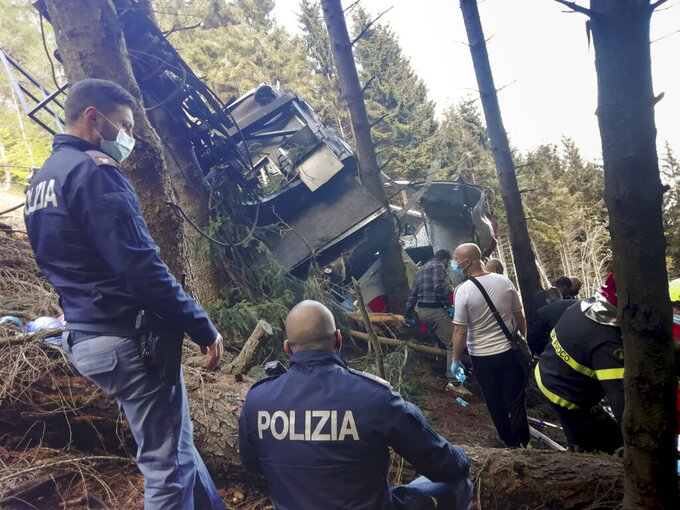 Rescuers work by the wreckage of a cable car after it collapsed near the summit of the Stresa-Mottarone line in the Piedmont region, northern Italy, Sunday, May 23, 2022. A cable car taking visitors to a mountaintop view of some of northern Italy's most picturesque lakes plunged to the ground Sunday, killing at least nine people and sending two children to the hospital, authorities said. (Italian Police via AP)