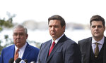 FILE - In this Jan. 17, 2019, file photo Florida Gov. Ron DeSantis, center, John Morgan, left, and Rep. Matt Gaetz, right, listen during a press conference at Kraft Azalea Garden in Winter Park, Fla. (Willie J. Allen Jr./Tampa Bay Times via AP, File)