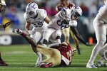 Boston College running back Travis Levy (23) tackles Kansas wide receiver Jamahl Horne (88) during the first half of an NCAA college football game in Boston, Friday, Sept. 13, 2019. (AP Photo/Michael Dwyer)