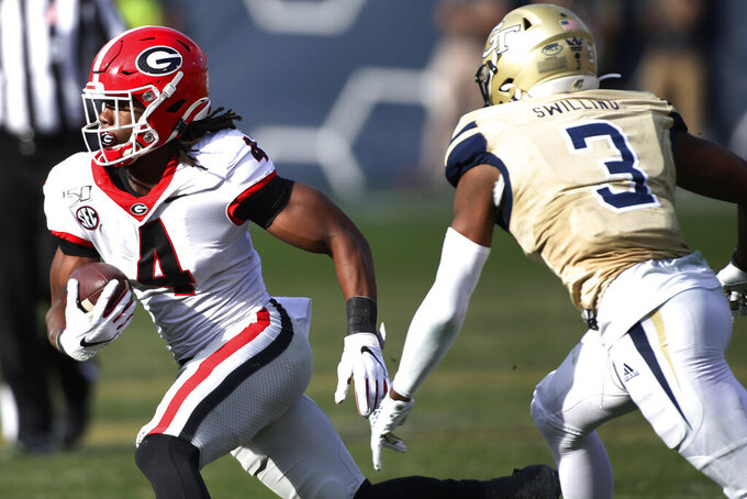 Georgia running back James Cook (4) moves the ball passed Georgia Tech defensive back Tre Swilling (3) in the second half of an NCAA football game between Georgia and Georgia Tech on Saturday, Nov. 30, 2019, in Atlanta. Georgia won 52-7. (Joshua L. Jones/Athens Banner-Herald via AP)