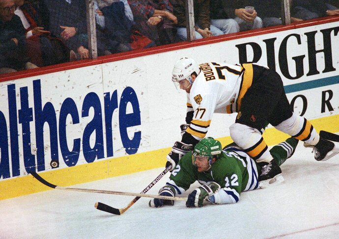 FILE - In this Dec. 13, 1990 file photo, Boston Bruins defenseman Ray Bourque (77) reaches over the back of Hartford Whaler Dean Evason (12) trying to get to the puck behind Boston's goal during first period action in the Boston. The NHL hasn't had best-of-five playoff series since 1986. That's changing for this year with the league expanding to 24 playoff teams as part of its restart. The qualifying round will feature 16 teams facing off in best-of-five series to determine who moves on. (AP Photo/Stephan Savoia, File)