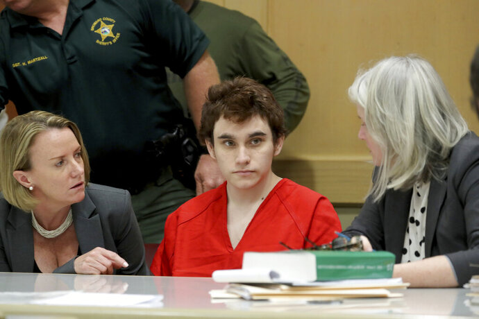 Parkland school shooting suspect Nikolas Cruz in court at the Broward Courthouse in Fort Lauderdale, Fla., Tuesday, May 1, 2019 for motion by the Public Defender's Office to withdraw from the case due to Cruz receiving an inheritance that can be used to pay for a private attorney. Defense attorney Melisa McNeill and Diane Cuddihy speak with their client. Nikolas Cruz, who faces the death penalty if convicted. Cruz is accused of killing 17 and wounding 17 in the February 2018 mass shooting at Marjory Stoneman Douglas High School in Parkland, Fla. (Mike Stocker/South Florida Sun-Sentinel via AP, Pool)