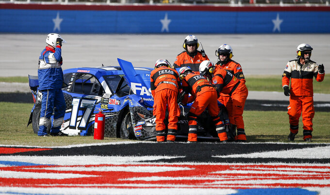 Safety personal secure Ricky Stenhouse Jr.'s car after a wreck exiting Turn 4 and ending in the grass on the front stretch during a NASCAR Cup Series auto race at Texas Motor Speedway, Sunday, Nov. 3, 2019, in Fort Worth, Texas. (AP Photo/Brandon Wade)