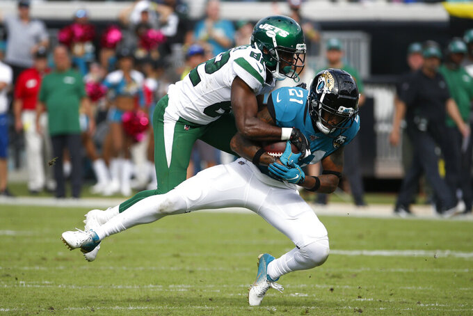 Jacksonville Jaguars cornerback A.J. Bouye (21) is tackled by New York Jets wide receiver Jamison Crowder, left, after an interception during the second half of an NFL football game, Sunday, Oct. 27, 2019, in Jacksonville, Fla. (AP Photo/Stephen B. Morton)