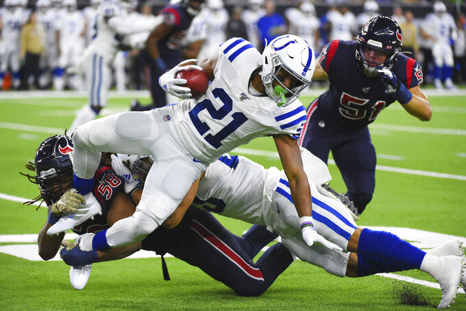 Indianapolis Colts running back Nyheim Hines (21) is upended by Houston Texans linebacker Peter Kalambayi (58) during the first half of an NFL football game Thursday, Nov. 21, 2019, in Houston. (AP Photo/Eric Christian Smith)