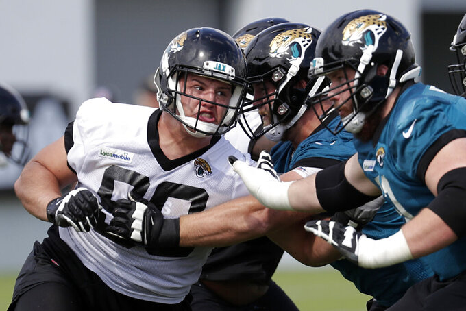 FILE - In this June 11, 2019, file photo, Jacksonville Jaguars defensive tackle Taven Bryan, left, rushes the offensive line during an NFL football practice, in Jacksonville, Fla. The defensive tackle and 2018 first-round draft pick is expected to be in the starting lineup again Thursday night, Aug. 29, 2019,  when the Jaguars (0-3) host the Atlanta Falcons (0-4) in the preseason finale for both teams. (AP Photo/John Raoux, File)
