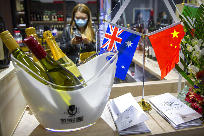 A staff member wearing a face mask stands near a display of Australian wines at the China International Import Expo in Shanghai, Thursday, Nov. 5, 2020. Chinese leaders are conducting an import fair under intensive anti-coronavirus controls in their latest effort to revive the world's No. 2 economy while the United States and Europe struggle with a renewed surge of infections. (AP Photo/Mark Schiefelbein)
