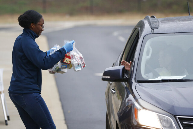 Volunteer Michaela Lawrence hands out meals to families with students at Hilsman Middle School in Athens, Ga., on Tuesday, March 17, 2020. Meals will be handed out each morning from 8:00a.m. to 10:00p.m. at Hilsman Middle School in Oglethorpe Elementary as well as others delivered by bus due to caronavirus.  (Joshua L. Jones/Athens Banner-Herald via AP)