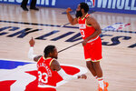 James Harden, right, and Robert Covington, left, of the Houston Rockets react during the first half of an NBA basketball game Tuesday, Aug. 4, 2020, in Lake Buena Vista, Fla. (Kevin C. Cox/Pool Photo via AP)