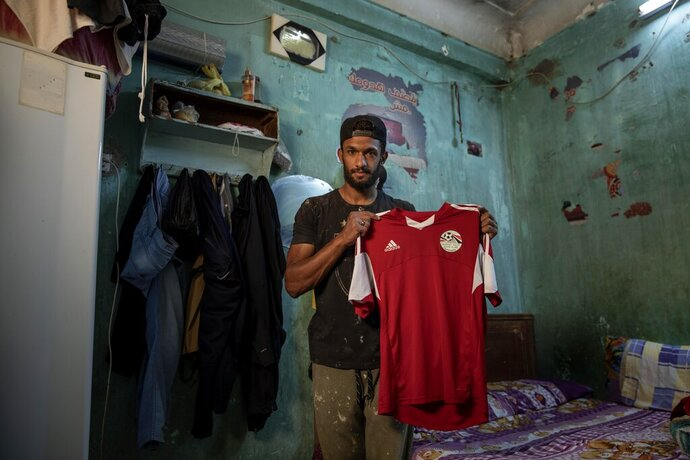 In this May 9, 2020 photo, 28-year-old defender Mahrous Mahmoud holds up his Egyptian national football team jersey he trains with, inside his home, in Manfalut, a town 350 kilometers (230 miles) south of Cairo in the province of Assiut, Egypt. Mahmoud should be on the field at this time of year playing as a defender for Beni Suef, a club in Egypt's second division. But like millions in the Arab world's most populous country, he has been hit hard by the coronavirus pandemic. (AP Photo/Nariman El-Mofty)