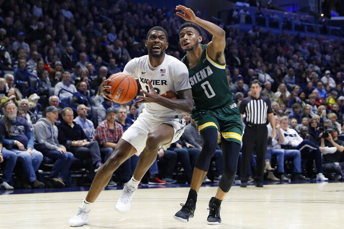 Xavier's Naji Marshall, left, drives against Siena's Donald Carey (0) during the first half of an NCAA college basketball game Friday, Nov. 8, 2019, in Cincinnati. (AP Photo/John Minchillo)