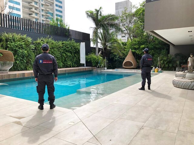 In this photo distributed by Colombia's Attorney Generals Office, officials pose with their backs to the camera by a pool on a property allegedly belonging to Alex Saab in Barranquilla, Colombia, Wednesday, July 22, 2020. Authorities seized a luxury mansion allegedly belonging to the businessman detained in Cape Verde on U.S. corruption charges related to Venezuelan President Nicolás Maduro. (Colombia's Attorney Generals Office via AP)