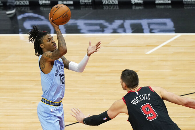 Memphis Grizzlies guard Ja Morant, left, shoots as Chicago Bulls center Nikola Vucevic defends during the first half of an NBA basketball game in Chicago, Friday, April 16, 2021. (AP Photo/Nam Y. Huh)