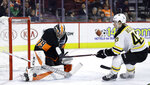 Philadelphia Flyers' Carter Hart, left, blocks a shot by Boston Bruins' Danton Heinen during the first period of an NHL hockey game, Wednesday, Jan. 16, 2019, in Philadelphia. (AP Photo/Matt Slocum)