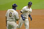 Milwaukee Brewers' Justin Smoak, right, is congratulated by third base coach Ed Sedar after hitting a two-run home run during the third inning of a baseball game against the Cincinnati Reds, Monday, Aug. 24, 2020, in Milwaukee. (AP Photo/Aaron Gash)