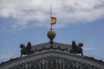 A Spanish flag hoisted to half-staff for the victims of COVID-19, flutters atop of the dome of the Atocha train station in Madrid, Spain, Tuesday, May 26, 2020. The Spanish government has declared 10 days of mourning starting Wednesday for the nearly 27,000 people who have died with the novel coronavirus in Spain, the longest official mourning period in the country's 4-decade-old democracy. (AP Photo/Bernat Armangue)