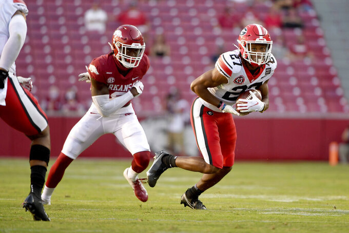 Georgia defensive back Eric Stokes (27) intercepts a pass intended for Arkansas' Mike Woods, left, during the second half of an NCAA college football game in Fayetteville, Ark., Saturday, Sept. 26, 2020. (AP Photo/Michael Woods)