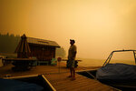 A business owner, who declined to give his name, looks up at the smoke-covered sky from the Creek Fire at his boat rental place Sunday, Sept. 6, 2020, in Shaver Lake, Calif. (AP Photo/Marcio Jose Sanchez)