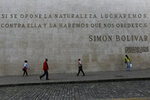 People walk past a quote by Simon Bolivar that reads in Spanish: