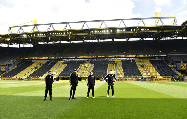 Referee Deniz Aytekin, 2nd left, and his team stand on the pitch before the German Bundesliga soccer match between Borussia Dortmund and Schalke 04 in Dortmund, Germany, Saturday, May 16, 2020. The German Bundesliga becomes the world's first major soccer league to resume after a two-month suspension because of the coronavirus pandemic. (AP Photo/Martin Meissner, Pool)