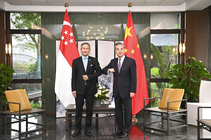 In this photo released by Xinhua News Agency, Chinese Foreign Minister Wang Yi, right, bumps elbows with Singaporean Foreign Minister Vivian Balakrishnan in Nanping City, southeast China's Fujian Province Thursday, March 31, 2021. The Chinese Foreign Minister is meeting with his counterparts from four Asian countries including Singapore, Malaysia, Indonesia and Philippine in southeastern China. (Li Xiang/Xinhua via AP)