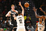 Atlanta Hawks guard Kevin Huerter passes the ball as Brooklyn Nets guard Joe Harris (12) defends during the first half of an NBA basketball game Wednesday, Dec. 4, 2019, in Atlanta. (AP Photo/John Amis)