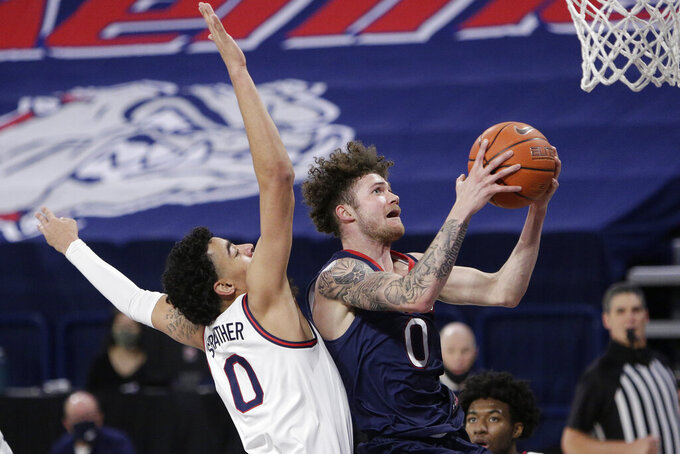 Saint Mary's guard Logan Johnson, right, shoots in front of Gonzaga guard Julian Strawther during the second half of an NCAA college basketball game in Spokane, Wash., Thursday, Feb. 18, 2021. (AP Photo/Young Kwak)