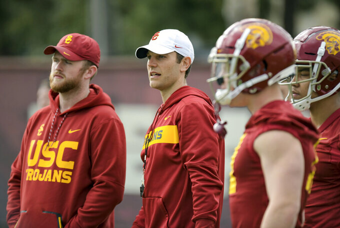 In this Tuesday, March 5, 2019 photo, provided by University of Southern California Athletics, new USC offensive coordinator Graham Harrell, center, watches during NCAA college football practice in Los Angeles. Harrell stepped into one of the highest-profile assistant jobs in college football after Kliff Kingsbury left USC without calling a play. The Trojans' new offensive coordinator is working hard to get up to speed in spring practice. (John McGillen/USC Athletics via AP)